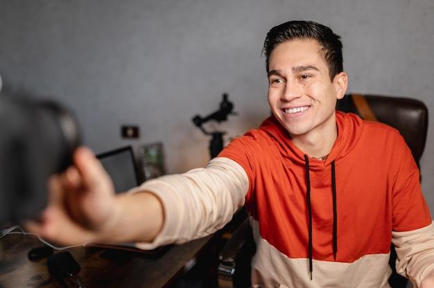 Giovane uomo sorridente che imposta la fotocamera e altre apparecchiature professionali per fare un video alla scrivania in ufficio. vlog, concetto di lavoro freelance.