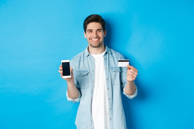 Giovane uomo sorridente che mostra lo schermo dello smartphone e la carta di credito, il concetto di shopping online o operazioni bancarie