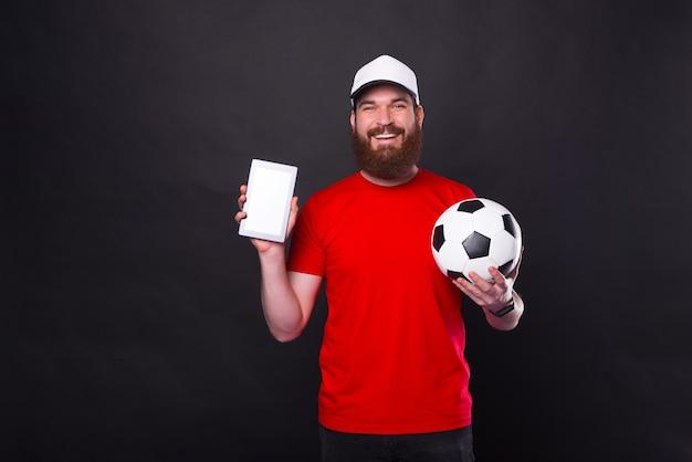 Giovane uomo sorridente che mostra tablet e tenendo il pallone da calcio sul nero