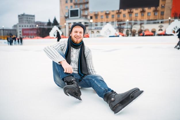 Giovane uomo sorridente in pattini che si siedono sul ghiaccio, pista di pattinaggio. pattinaggio su ghiaccio invernale all'aria aperta, tempo libero attivo