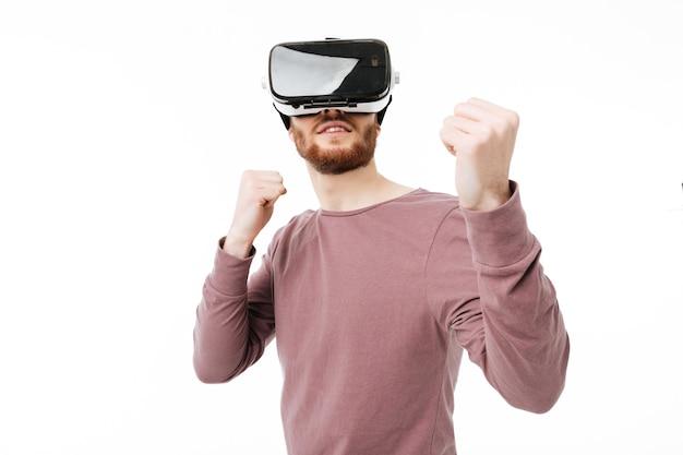 Giovane uomo sorridente che indossa occhiali per realtà virtuale