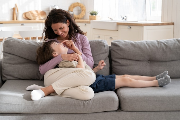 La giovane madre sorridente abbraccia il ragazzo carino sdraiato sulle ginocchia sul divano e si diverte a passare il tempo a casa con il figlio