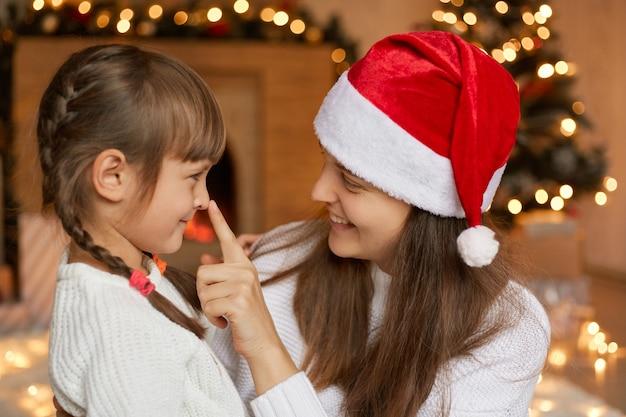 Giovane madre sorridente e piccola figlia che giocano a natale, guardandosi con amore