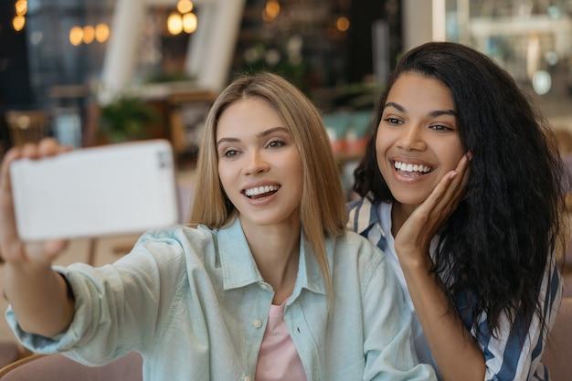 Giovani amici multirazziali sorridenti che prendono selfie, utilizzando il telefono cellulare, divertendosi insieme