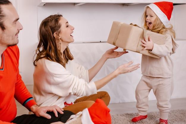 Giovani genitori sorridenti che danno piccola figlia divertente presente a natale, ragazza di risata in scatola della tenuta del cappello della santa nelle mani. vacanza in famiglia. vacanze, regali, natale, concetto di natale
