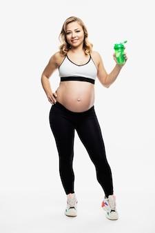 Giovane donna bionda incinta sorridente in stand di abbigliamento sportivo. maternità sana. a tutta altezza. isolato sulla parete bianca. verticale.