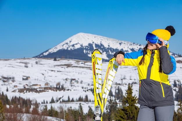 Giovane sci grazioso sorridente della tenuta della donna. montagne sullo sfondo. viaggio invernale. copia spazio