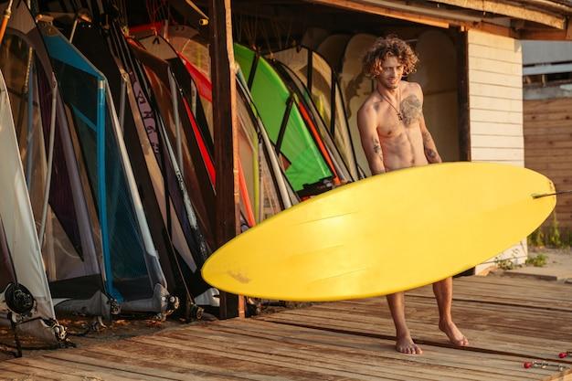 Giovane surfista professionista sorridente che tiene la tavola da surf alla baracca
