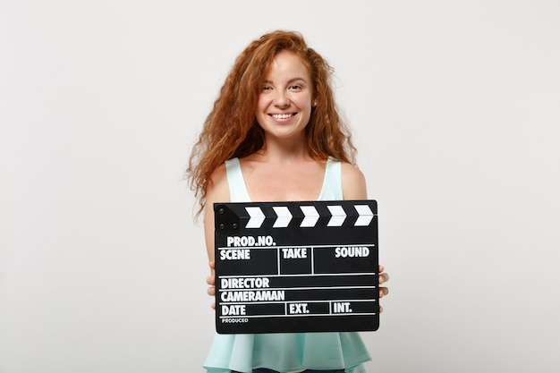 Giovane ragazza sorridente della donna della testarossa in vestiti leggeri casuali che posano isolato su fondo bianco in studio. concetto di stile di vita della gente. mock up copia spazio. tenendo il classico ciak nero per la produzione di film.