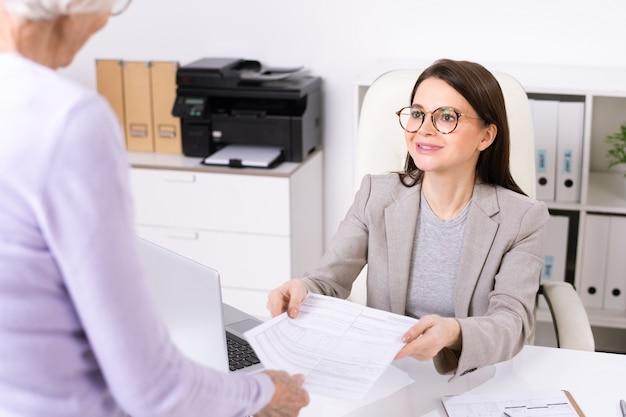 Giovane segretaria o receptionist sorridente in abiti da cerimonia che passa un documento a uno dei clienti senior chiedendole di compilarlo