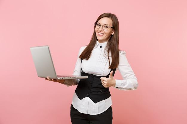 Giovane donna d'affari di successo sorridente con gli occhiali che lavora in un computer portatile che mostra pollice in su isolato su sfondo rosa pastello. signora capo. concetto di ricchezza di carriera di successo. copia spazio per la pubblicità.