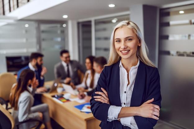 Giovani sorridenti di successo splendida bionda imprenditrice in abbigliamento formale in piedi nella sala del consiglio con le braccia incrociate e guardando la fotocamera. sullo sfondo i suoi colleghi che hanno riunione.