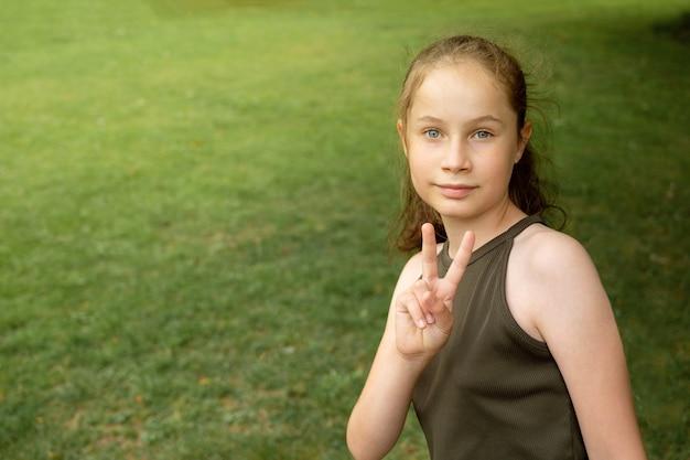 Giovane ragazza sorridente dell'adolescente che mostra il segno di pace sul fondo verde e all'aperto del parco