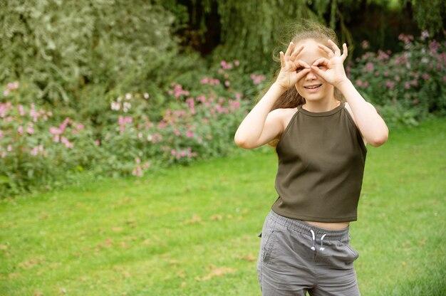 Giovane ragazza sorridente dell'adolescente che mostra il segno con le mani, sul fondo verde e all'aperto del parco
