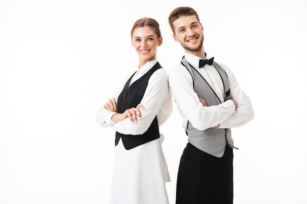 Il giovane cameriere e cameriera sorridenti in camicie bianche e canottiere se ne stavano in piedi schiena contro schiena mentre gioiosamente