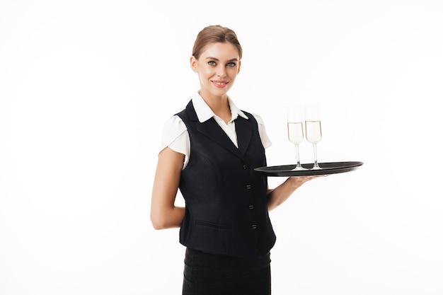 Giovane cameriera sorridente in uniforme tenendo il vassoio con gli occhiali sognante