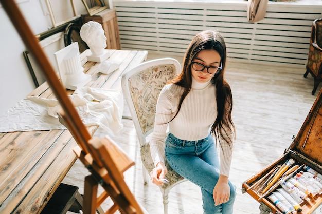Giovane artista donna sorridente, con in mano il pennello e disegna su tela, lavorando in uno studio d'arte domestico.