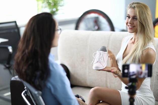 La giovane donna sorridente blogger tiene le scarpe sportive nelle mani davanti alla telecamera con un amico a casa