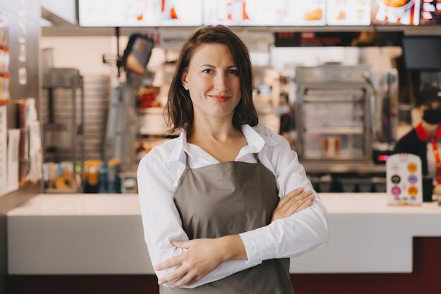 Una giovane donna d'affari sorridente in un grembiule si trova in un caffè di fronte a una vetrina, le braccia incrociate, guardando la telecamera.
