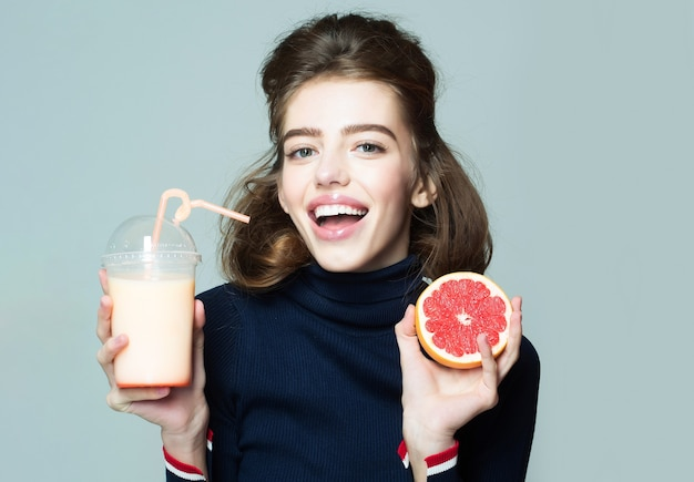 La giovane donna sorridente o la ragazza sexy sveglia tiene la frutta del pompelmo che beve il succo fresco dalla bottiglia o dal vetro con le pose della paglia sullo spazio grigio della copia