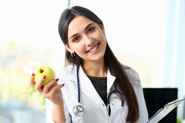 Il giovane medico sorridente della donna tiene la mela
