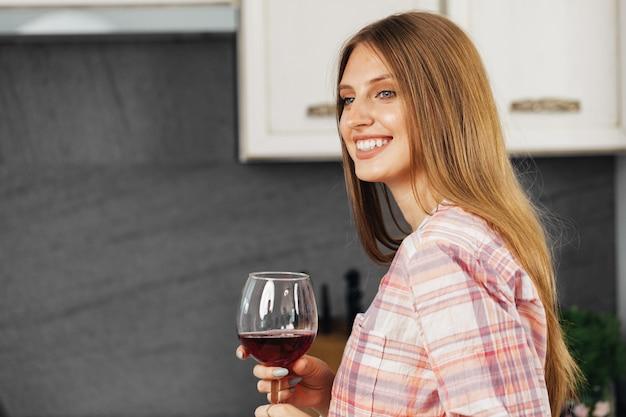 Giovane donna sorridente che beve vino in cucina, ritratto