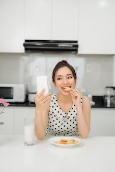 Giovane donna sorridente che mangia biscotti e sorride, utilizzando lo smartphone. colazione salutare.