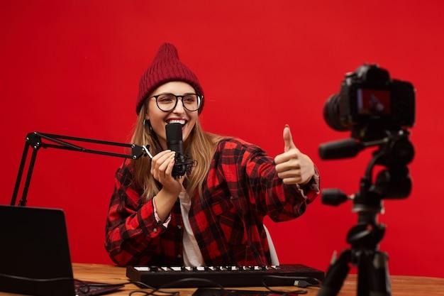 Giovane donna sorridente in occhiali da vista che mostra il pollice fino alla telecamera e cantando che riprende il contenuto