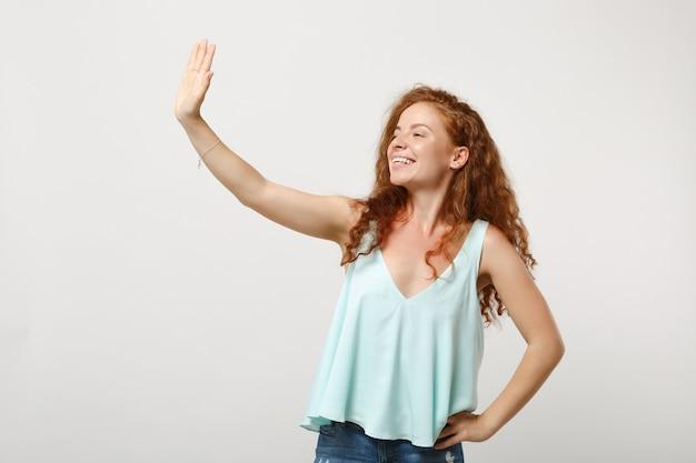 Giovane ragazza sorridente della donna in vestiti leggeri casuali che posano isolato sul fondo bianco della parete. concetto di stile di vita della gente. mock up copia spazio. in piedi con la mano tesa per salutare, guardando da parte.