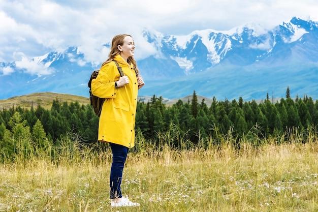 Giovane donna sorridente escursionista con uno zaino si trova sullo sfondo delle montagne