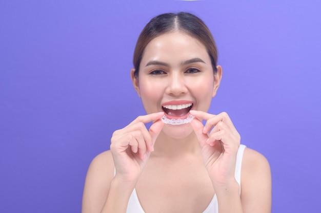 Una giovane donna sorridente che tiene bretelle invisalign in studio, assistenza sanitaria dentale e concetto ortodontico.