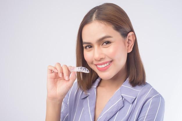 Una giovane donna sorridente che tiene bretelle invisalign su bianco