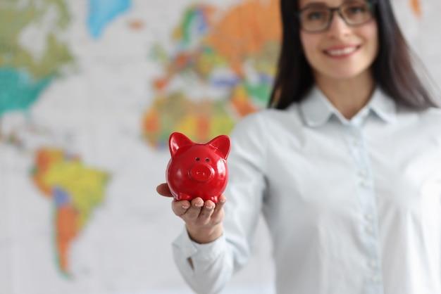 Giovane donna sorridente che tiene salvadanaio di maiale rosso sullo sfondo della mappa del mondo