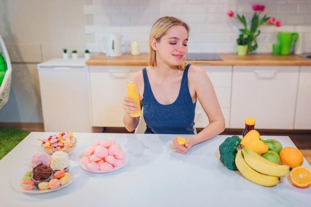 La giovane donna sorridente tiene l'acqua di disintossicazione mentre sceglie tra cibo sano e malsano in cucina.