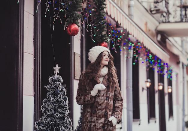 Giovane donna sorridente in guanti e cappello lavorato a maglia a piedi in città