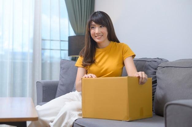 Una giovane donna sorridente che apre una scatola di cartone nel soggiorno di casa