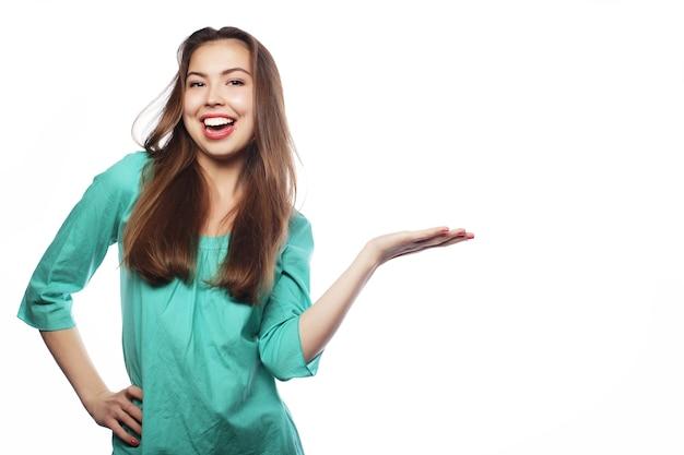 La giovane donna sorridente indica una mano con un'espressione facciale positiva. isolato su bianco