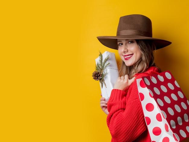 Giovane donna sorridente in maglione rosso con confezione regalo e shopping bag sulla parete gialla