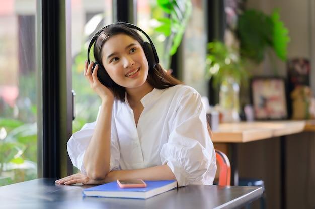 Giovane donna sorridente, rilassarsi e ascoltare musica con le cuffie
