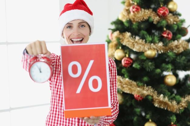 La giovane donna sorridente con il cappello di babbo natale tiene la sveglia e il poster con la percentuale sullo sfondo