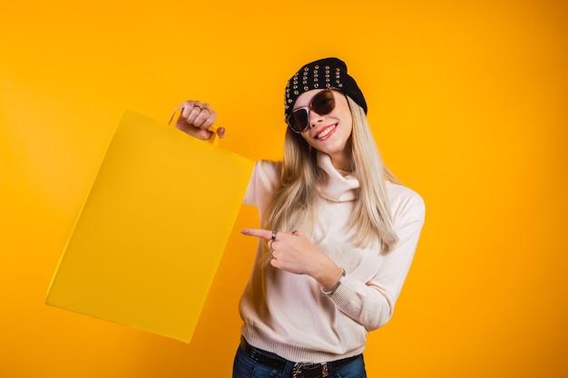 Giovane donna sorridente che mostra una borsa della spesa su sfondo giallo.
