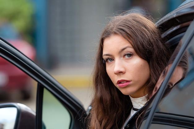 Giovane donna sorridente si siede in una macchina con una porta aperta e guarda indietro, ritratto del primo piano