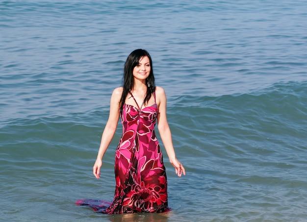 Giovane donna sorridente in piedi nelle onde del mare
