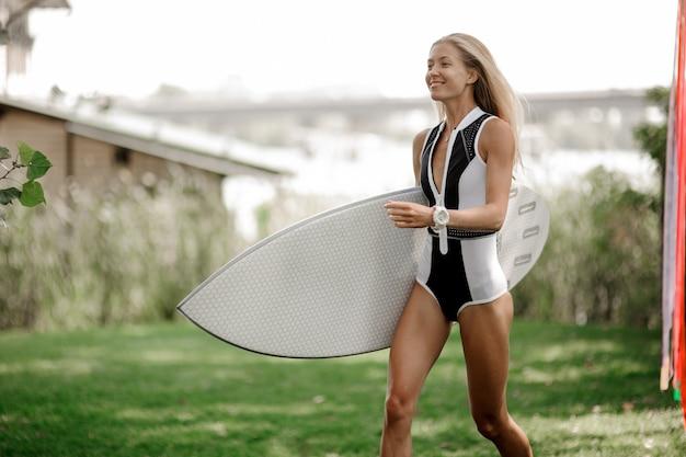 Giovane donna sorridente in costume da bagno con un wakeboard sul prato