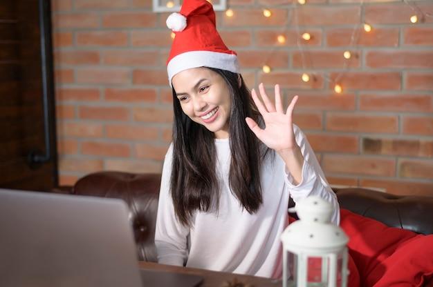 Una giovane donna sorridente che indossa il cappello rosso di babbo natale che fa videochiamata sui social network con la famiglia e gli amici il giorno di natale.