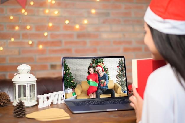 Una giovane donna sorridente che indossa il cappello rosso di babbo natale che effettua una videochiamata sul social network con la famiglia e gli amici il giorno di natale.