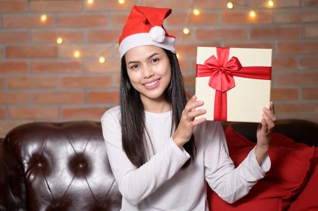 Una giovane donna sorridente che indossa il cappello rosso di babbo natale che mostra una confezione regalo il giorno di natale