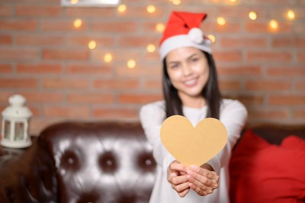 Una giovane donna sorridente che indossa il cappello rosso di babbo natale che mostra un modello a forma di cuore il giorno di natale, il concetto di vacanza.