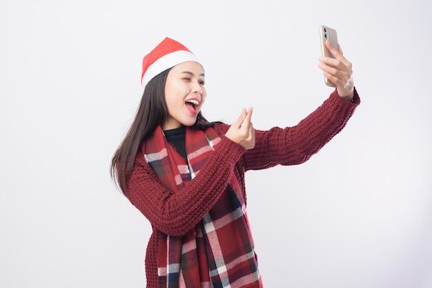 Una giovane donna sorridente che indossa il cappello rosso di babbo natale prendendo un selfie su sfondo bianco studio.