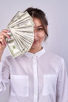 Giovane donna sorridente con banconote di dollari isolate su white